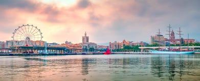 Malaga port panorama with ferris wheel and saiiling cruise ship. Malaga, Spain - April 26, 2018. Malaga port panorama with ferris wheel and saiiling cruise ship Stock Image