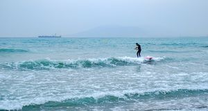 A man paddling on a surfboard in the open sea. Malaga, Spain - April 21, 2018. A man paddling on a surfboard in the open sea, Malaga, Spain Royalty Free Stock Photography