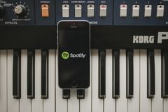 MALAGA, SPAIN - APRIL 12 th, 2018: Spotify Streaming music app in an iPhone screen, placed on a vintage musical keyboard. Spotify is a music, podcast, and video royalty free stock images