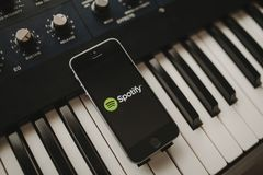 MALAGA, SPAIN - APRIL 12 th, 2018: Spotify Streaming music app in an iPhone screen, placed on a vintage musical keyboard. Spotify is a music, podcast, and video stock image