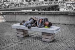 Homeless man sleeps on the stone bench in downtown. Malaga, Spain - August 03, 2018. Homeless man sleeps on the stone bench in downtown stock photography
