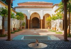 MALAGA, SPAIN - FEBRUARY 16, 2014: A quiet yard at Alcazaba, a c. Astle of Malaga, with orange trees at pots, fountains and arch entrance in arab style Stock Photos