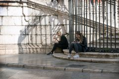 Malaga, Spain, February 2019.Two girls relax on the marble steps of the famous Malagan Incarnate Cathedral and eat ice cream. royalty free stock photo