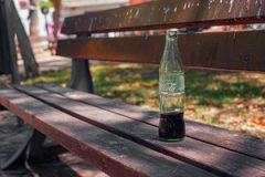 The Coca Cola bottle on the bench in the park. Malaga, Spain - July 21, 2018. The Coca Cola bottle on the bench in the park royalty free stock photo