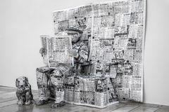 A man dressed in newspapers and his dog. Malaga, Spain - June 02, 2018. A man dressed in newspapers read the newspaper and his dog on the Marques de Larios Stock Image