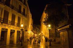 Malaga, Spain - June 24: Tourists walk past the dimly lit street. Of Malaga, Spain, Europe Stock Photos