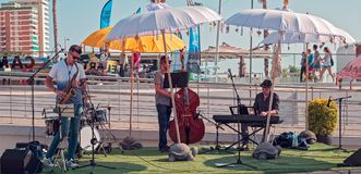 Band of musicians performing live. Malaga, Spain - May 18, 2018. Band of musicians performing live in walk Muelle Uno, Malaga, Spain Stock Image