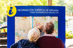 MALAGA, SPAIN - NOVEMBER 15, 2014: A couple of senior tourist consulting a map of the city. royalty free stock images