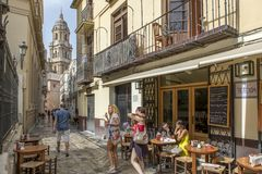 MALAGA, SPAIN - September 2nd, 2018: Tourists having a tea in a coffee shop with the Cathedral in the background in Malaga, Spain. royalty free stock images