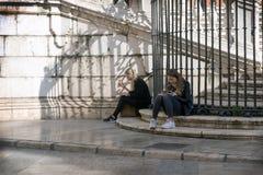 Malaga Spanien, Februari 2019 Tv? flickor kopplar av p? marmormomenten av den ber?mda Malaganen f?r att f?rverkliga domkyrkan och royaltyfri foto