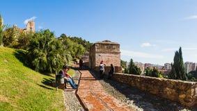 MALAGA SPANIEN - NOVEMBER 15, 2014: Alcazabaen arbeta i trädgården med någon turist som tycker om solen och sikterna Royaltyfri Foto