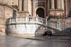 Malaga, Spanje, Februari 2019 Twee meisjes ontspannen op de marmeren stappen van beroemde Malagan gestalte geven aan Kathedraal e stock afbeelding