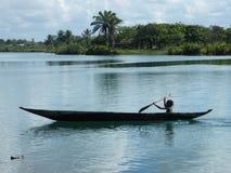 Malagasy child steering canoe Royalty Free Stock Photo