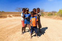 Malagasy cool guys. Group of curious local kids posing in front of the camera for some candy in Isalo, Madagascar, on September 9, 2013 royalty free stock photo