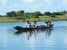 Malagasy family crossing river by canoe stock image