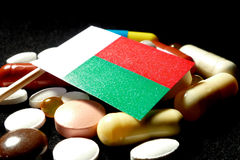 Malagasy flag with lot of medical pills isolated on black background Royalty Free Stock Photography