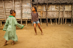 Malagasy girls playing. Two young malagasy girls or sisters playing together in the courtyard in front of their wooden hut, Madagascar Royalty Free Stock Photos