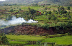 Malagasy landscape with smoke from fire. Royalty Free Stock Image