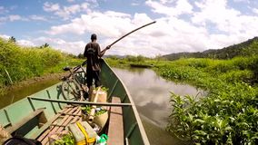Malagasy man from village on Madagascar helping ride boat transporting freight