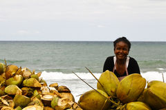 Malagasy woman selling coconuts on the beach Stock Image