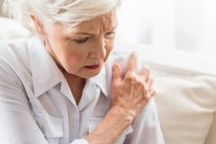 Elderly woman is enduring awful ache. Malaise. Aged lady is sitting on couch and feeling joint pain. She is touching her shoulder expressing suffering. Copy Stock Images