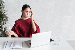 Elegant young girl is working in office and feeling unwell. Malaise. Portrait of Asian businesswoman is sitting at table with laptop and having terrible headache Stock Images