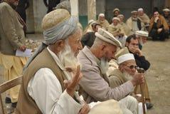 MALAK在椅子坐导致村民的问题 免版税库存图片