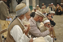 MALAK está sentando-se na cadeira para produzir os problemas dos aldeões imagens de stock royalty free