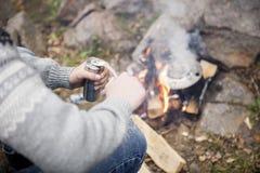 Malande kaffe för man nära brasa på campingplatsen Fotografering för Bildbyråer