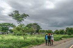 Trip through Angola& x27;s lands 2018: View of a three men chatting beside the road with traditional village and cloudy sky as. Malange / Angola - 12 08 2018 stock photography