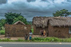 View of traditional village, people and thatched and zinc sheet on roof houses and terracotta brick walls royalty free stock photo