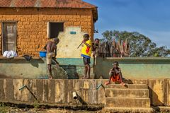 MALANJE/ANGOLA - 10. März 2018 - afrikanische Jungen, die im Wasserbrunnen, ländliches Gebiet von Afrika, Angola, Malanje spielen stockbild