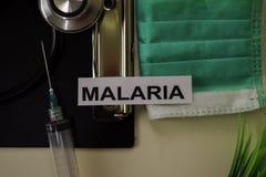 Malaria mit Inspiration und Gesundheitswesen/medizinisches Konzept auf Schreibtischhintergrund lizenzfreie stockfotos