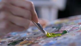Malarz miesza akrylową farbę na palecie z muśnięciem zbiory