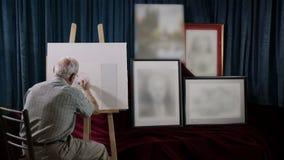Malarz przy pracą z mnóstwo obramiającymi obrazkami w pobliżu zdjęcie wideo