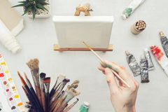 Malarz trzyma paintbrush w jego ręce Kanwa na artystycznym wyposażeniu na biurku i sztaludze fotografia stock