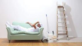 Malarza mężczyzna przy pracą, skończony działanie i kłama puszek na leżance zdjęcie wideo
