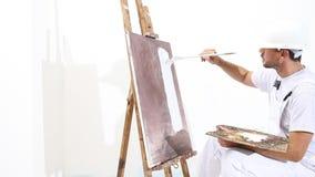Malarza mężczyzna przy pracą z farby muśnięciem, sztalugą, kanwą i paletą, ściennego obrazu pojęcie, biały tło zbiory