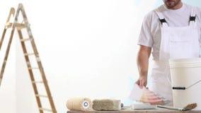 Malarza mężczyzna przy pracą z kolorów swatches próbkami, ściennego obrazu pojęcie, drabina w tle, muśnięcia i wiadro w dla, zdjęcie wideo