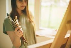 Malarza mienia paintbrushes i dopatrywanie kanwa zdjęcia royalty free