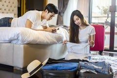 Malas de viagem asiáticas da embalagem do viajante dos pares da felicidade que preparam-se para Fotos de Stock Royalty Free