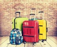 Malas de viagem e trouxa coloridas na parede de tijolo Imagem de Stock