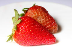Malas fresas rojas estropeadas sanas y putrefactas Fotografía de archivo