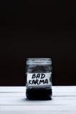 Malas karmas - una inscripción en la etiqueta de un tarro de cristal con un líquido del color negro en un fondo blanco y negro Foto de archivo libre de regalías
