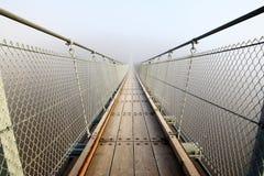 Malas perspectivas - puente colgante en la niebla fotos de archivo