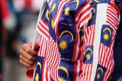 Malasio que sostiene la bandera malasia que lleva un mono de la bandera malasia Foto de archivo