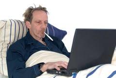 Malato in base con il computer portatile. Fotografia Stock Libera da Diritti