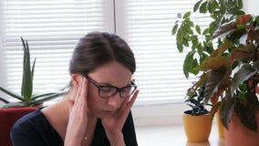 Malato sul lavoro - le giovani free lance femminili che hanno un'emicrania stock footage