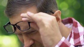 Malattia della cataratta, uomo con vista difficile che esamina telefono, cattivo montaggio della lente archivi video