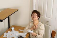 Malattia di sensibilità della donna più anziana con le sue fatture finanziarie Fotografia Stock